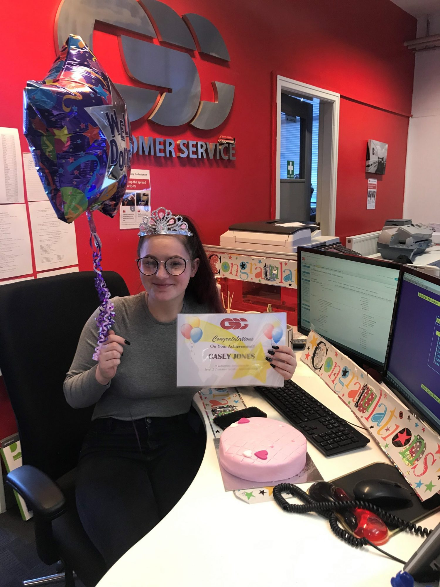 Casey Jones celebrating achieving Distinction on her Apprenticeship, with cake, balloons and a diploma